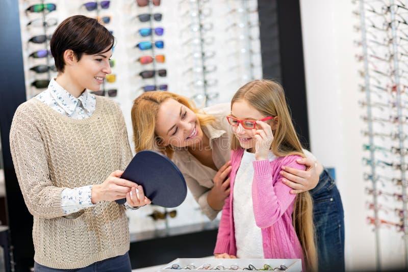 Sprzedawczyni chwyta lustro podczas gdy dziecko pr?by ramy dla eyeglasses obrazy royalty free