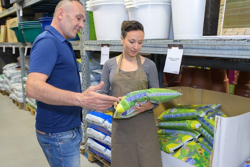 Sprzedawczyni poleca mężczyzna użyźniacz dla storczykowej rośliny w pepinierze obrazy stock
