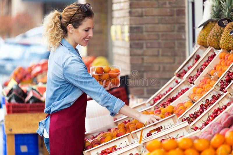 Sprzedawczyni wybiera świeżą owoc i przygotowywa dla pracującego dnia w fruitshop fotografia stock