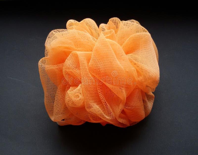 Spugna esfoliante arancio del bagno per un'esperienza casalinga di rilassamento della stazione termale Primo piano di una spugna  fotografie stock