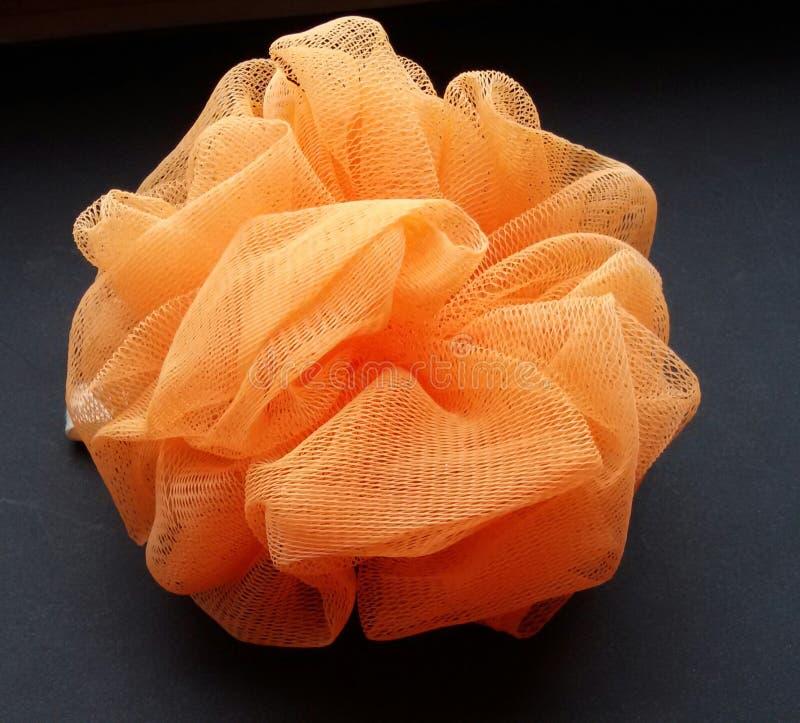 Spugna esfoliante arancio del bagno per un'esperienza casalinga di rilassamento della stazione termale Primo piano di una spugna  fotografia stock