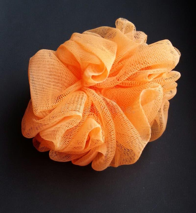 Spugna esfoliante arancio del bagno per un'esperienza casalinga di rilassamento della stazione termale Primo piano di una spugna  immagini stock