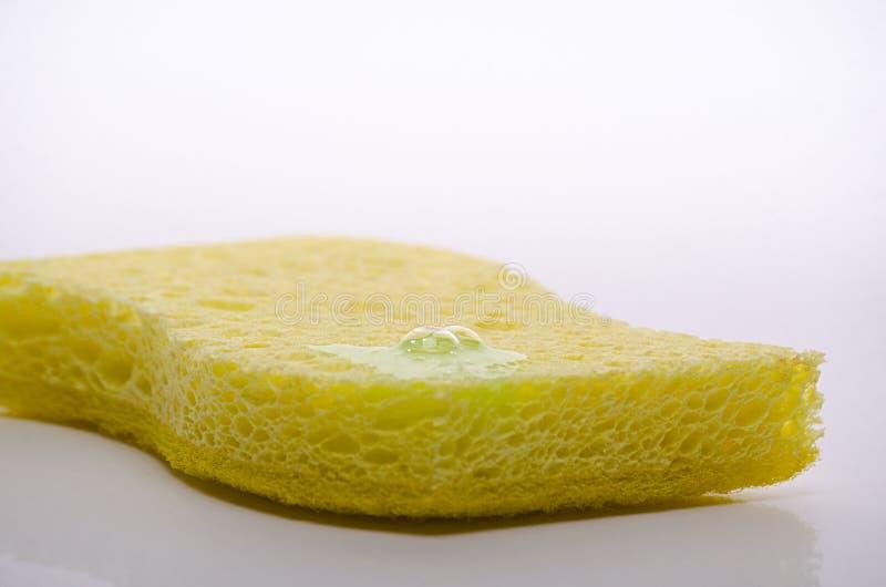 Spugna gialla per lavare i piatti con una goccia del detersivo, bolla di sapone, isolata su fondo bianco fotografie stock libere da diritti
