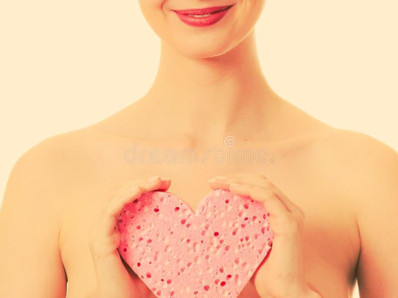 Spugna nuda del cuore della tenuta della donna immagini stock libere da diritti