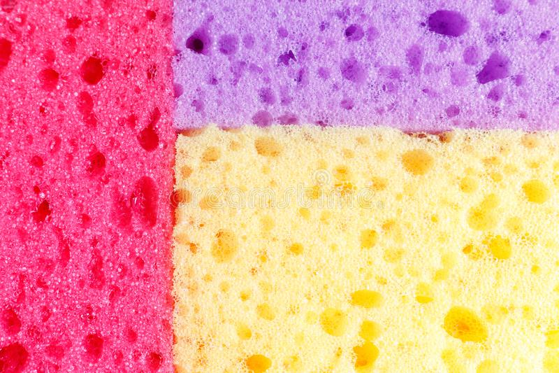 Spugne colorate per lavare i piatti ed altri bisogni domestici Vista da sopra La struttura delle spugne rosse, porpora ed arancio fotografie stock libere da diritti