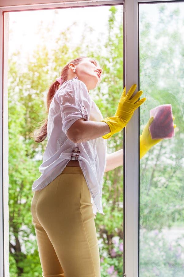 spugne del liquido di lavatura dei piatti di concetto di pulizia Finestra di lavaggio della giovane donna fotografie stock