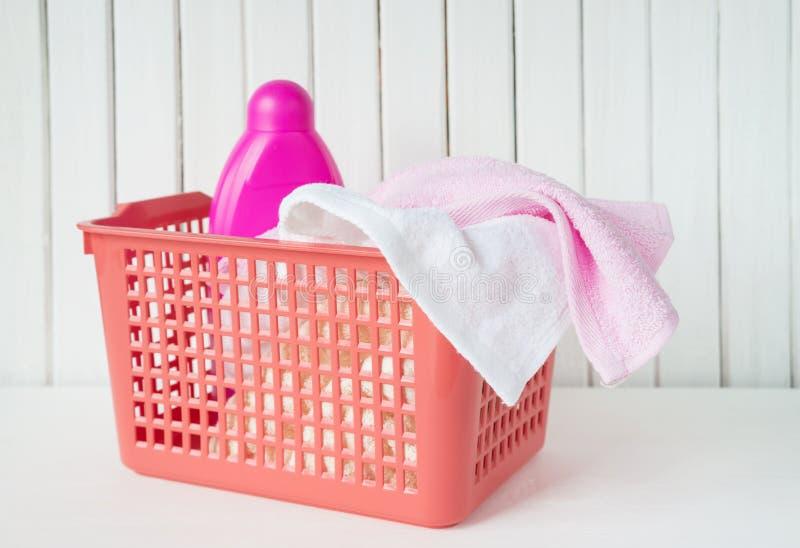 Spugne e detersivo nel canestro di lavanderia immagini stock