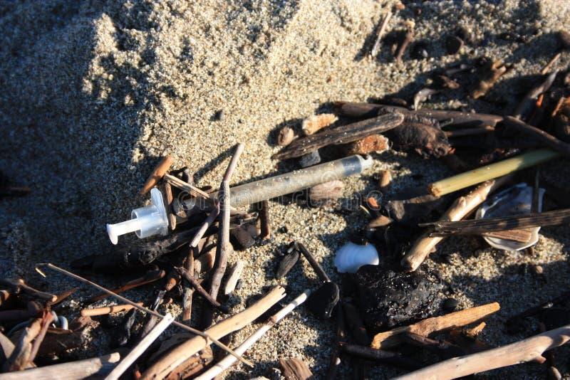 Spuit en andere die vuil bij het strand wordt verlaten stock foto's
