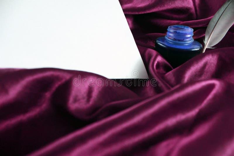 Spule auf purpurrotem Seidensatin mit Tinte und Weißbuch stockfotos
