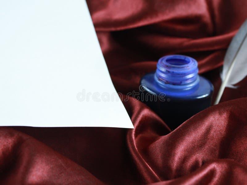 Spule auf Seidensatin mit Tinte und Weißbuch stockfotografie