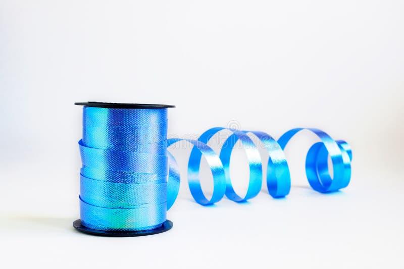Spule der blauen Windenbandrolle für Geschenkverpackungskunst und des Handwerks auf weißem Hintergrund Selektiver Fokus, Kopienra stockbild