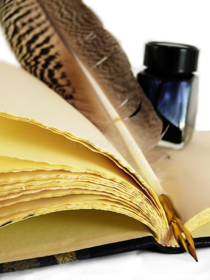 Spule u. Tintenfaß auf einem Buch lizenzfreie stockbilder