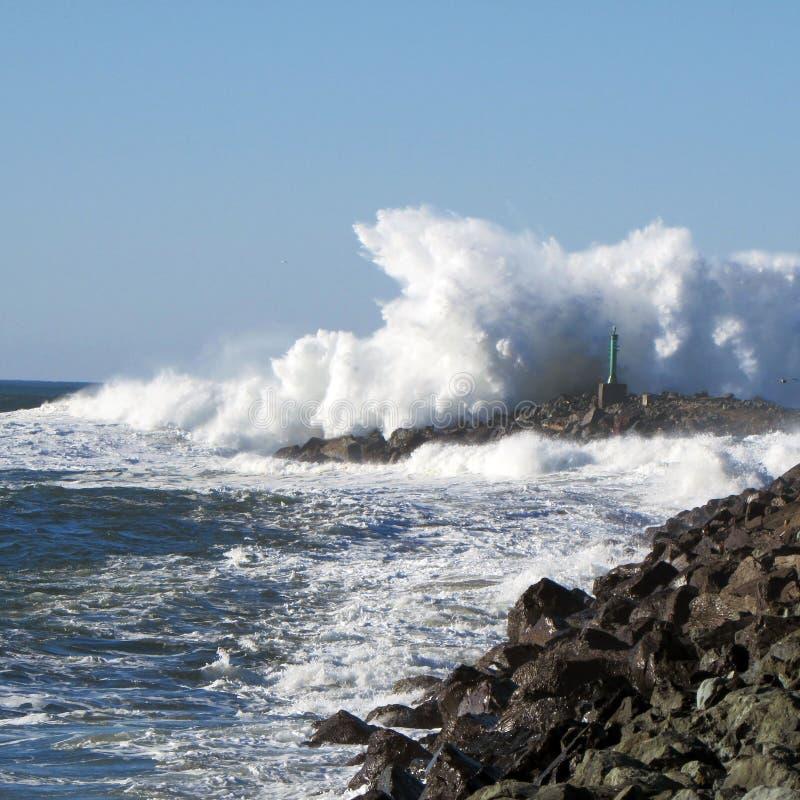 Spuma che si schianta sul molo dell'Oregon fotografia stock libera da diritti