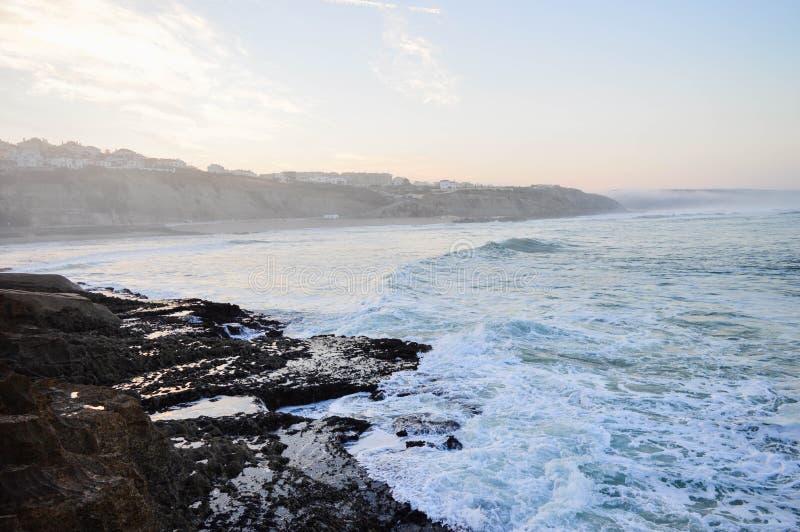 Spuma di mattina ad alba nell'oceano vicino alle grandi pietre fotografia stock libera da diritti