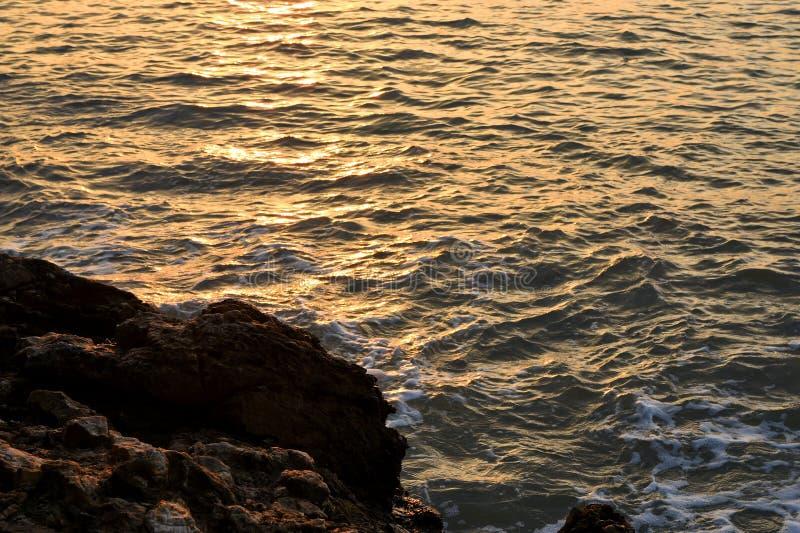 Spuma piacevole del mare con la pietra e l'effetto della luce di tramonto fotografia stock
