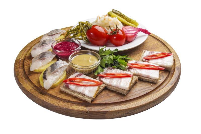 Spuntini assortiti per vodka Salo con senape e rafano Verdure marinate casalinghe Aringhe con le patate Sul rustico fotografia stock