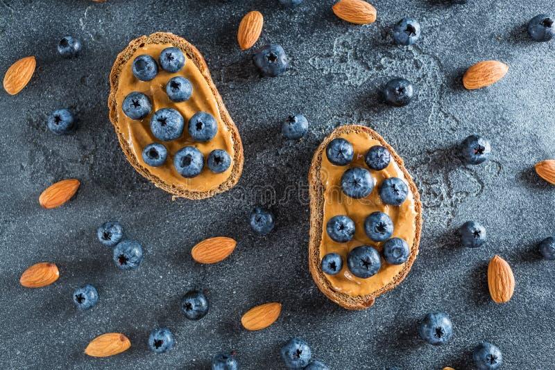 Spuntini con pane, burro di arachidi ed i mirtilli Concetto sano dell'alimento Disposizione piana, vista superiore immagini stock libere da diritti