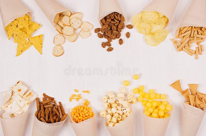 Spuntini croccanti luminosi dell'assortimento - nacho, crostini, chip, tortiglia, popcorn in cono di carta sulla plancia di legno fotografia stock