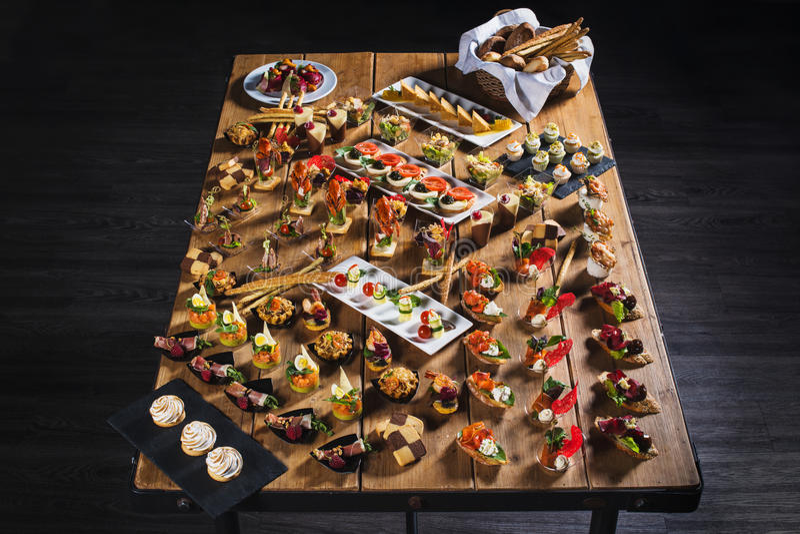Spuntini messi Brushettas, canape, insalate, dessert, tortini, oys immagini stock
