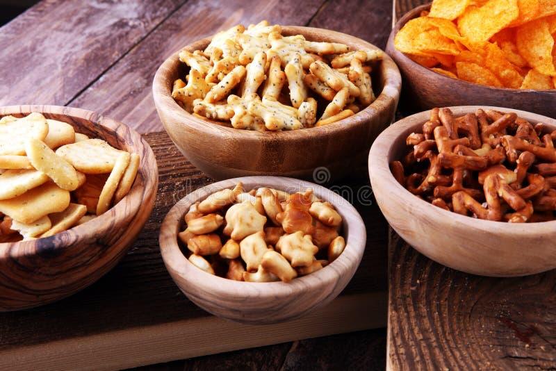 Spuntini salati Ciambelline salate, chip, cracker in ciotole di legno fotografia stock