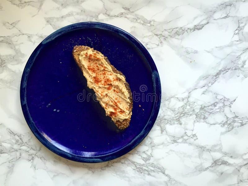 Spuntino del vegano: Intero pane tostato artigianale del grano con il hummus e la paprica fotografia stock
