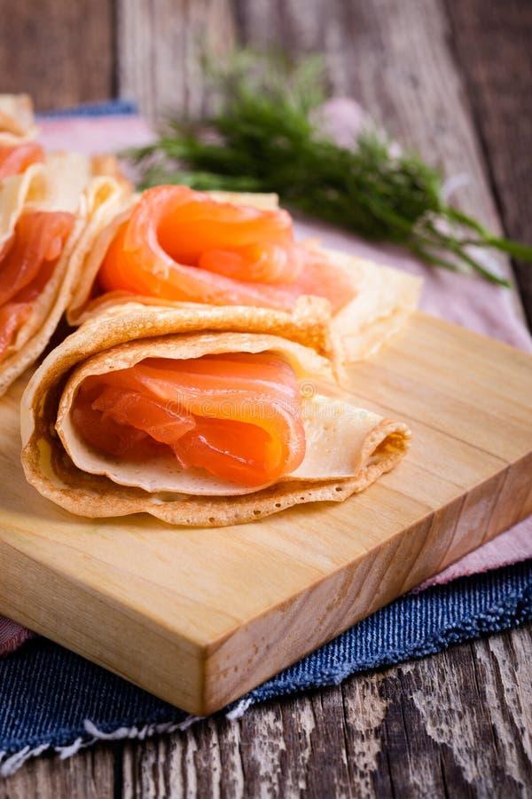 Spuntino di color salmone, crêpe farciti sul bordo di legno fotografia stock