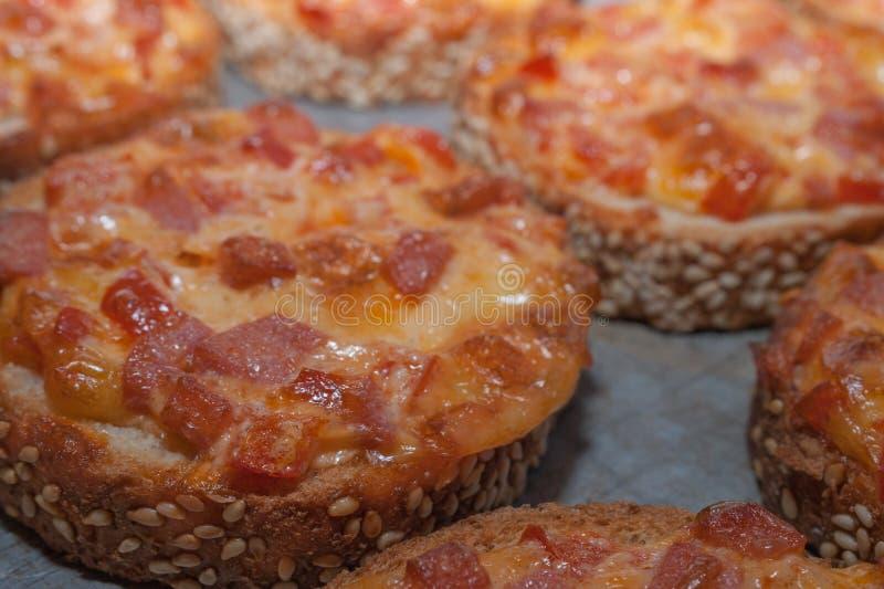 Spuntino facile rapido Pane del sesamo al forno con salame e formaggio su Oven Tray Mini pizza fotografia stock
