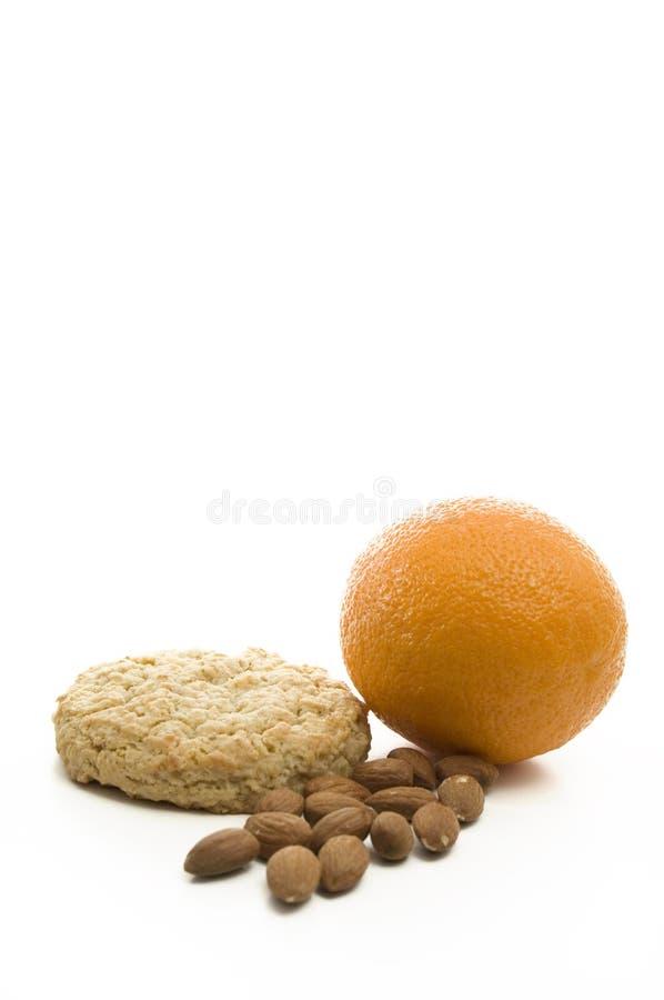 Spuntino leggero delle mandorle, del biscotto e dell'arancia su fondo bianco immagine stock