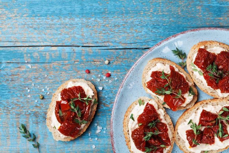 Spuntino Mediterraneo o aperitivo dalla Bruschetta, dal formaggio cremoso e dai pomodori seccati al sole Vista superiore fotografia stock libera da diritti