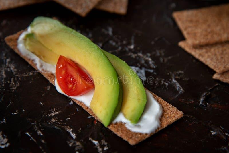 Spuntino sano dal cracker intero del pane croccante della segale con i pomodori ciliegia, l'avocado ed il yogurt su fondo nero fotografia stock libera da diritti