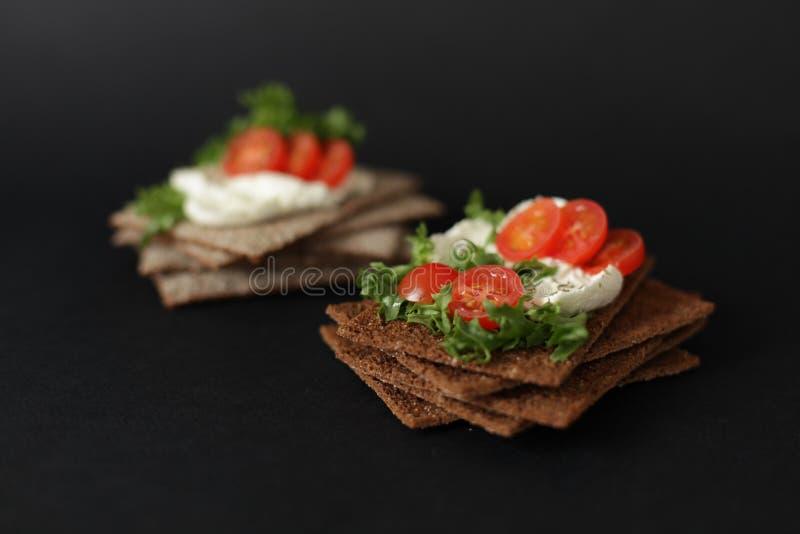 Spuntino sano dal cracker intero del pane croccante della segale con i pomodori ciliegia, l'insalata ed il formaggio a pasta moll immagini stock libere da diritti
