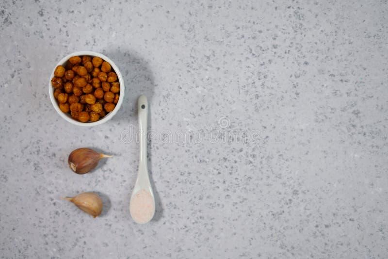 Spuntino sano del vegano, ceci arrostiti piccanti in ciotola Fuoco selettivo, spazio per testo immagine stock