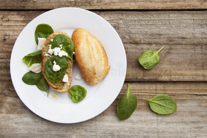 Spuntino sano Panino o pane con le foglie della pasta e del basilico di pesto Tavola di legno rustica, vista superiore immagine stock