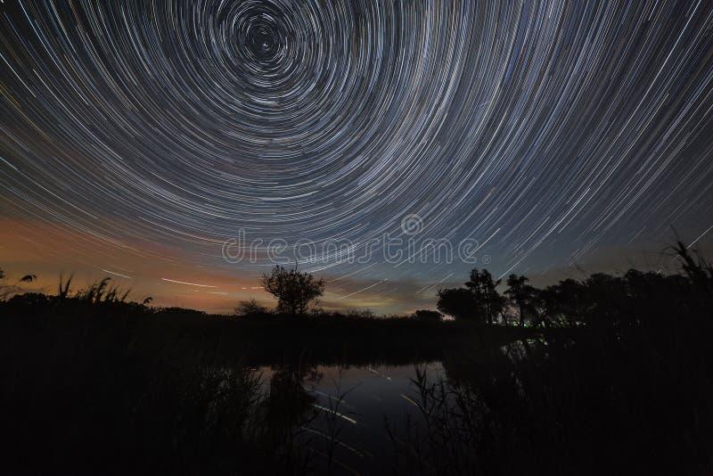 Spur von Sternen im nächtlichen Himmel mit den Wolken reflektiert im Fluss Bewegung im Raum fotografiert auf langer Belichtung lizenzfreie stockbilder