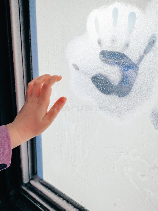 Spuren der Kinderhandpalme auf gefrorenem bereiftem Winterfenster stockfoto