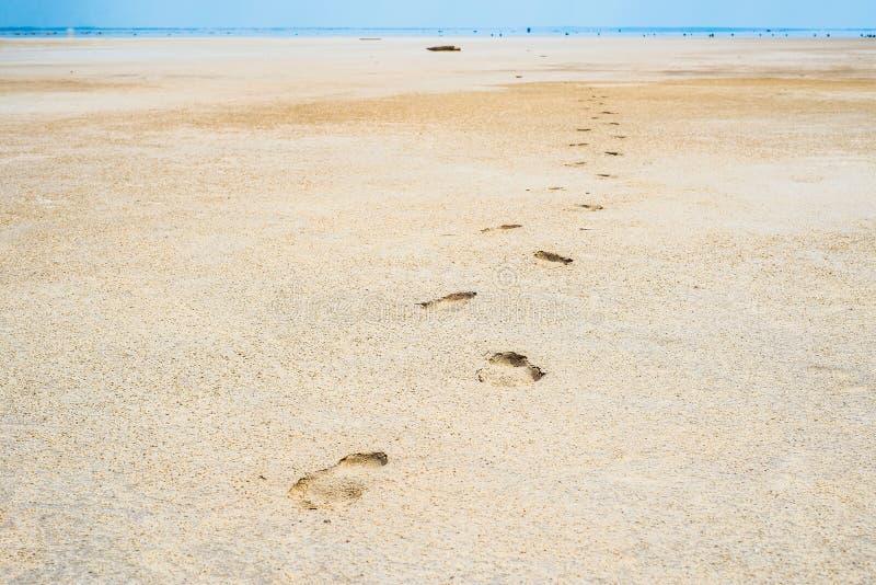 Spuren von den menschlichen Beinen, die in den Sand auf der Küstenuntiefe des salzigen Sees Baskunchak ausdehnen stockfotos