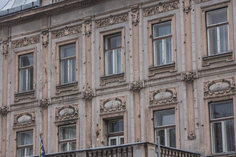 Spuren von den Schüssen, die auf der Fassade eines Wohngebäudes in Sarajevo nach dem Krieg bleiben Schattierte Entlastungskarte m stockbilder