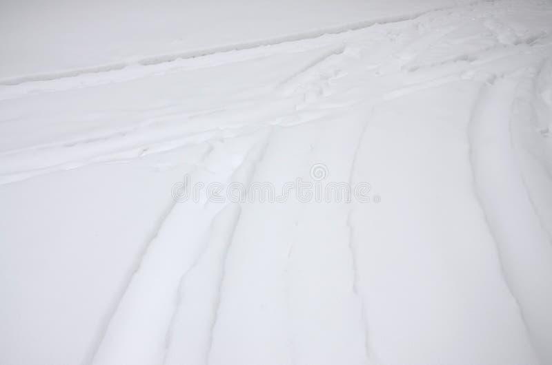 Spuren von den Wagenrädern auf einer schneebedeckten Straße Gefährliches und glattes Drehen des Fahrzeugs stockbilder