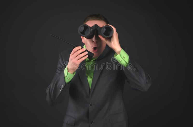 Spy. Bodyguard. Secret service agent. Amazed security agent spy is looking through a binoculars in his hand and is talking on the portable radio station royalty free stock images