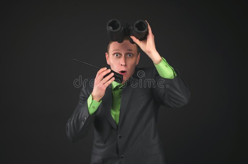 Spy. Bodyguard. Secret service agent. Amazed security agent spy is looking through a binoculars in his hand and is talking on the portable radio station royalty free stock image