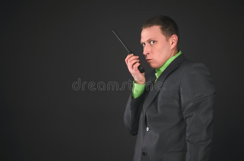 Spy. Bodyguard. Secret service agent. Security agent man is talking on the portable radio station and intently looking isolated on black background. Need royalty free stock images