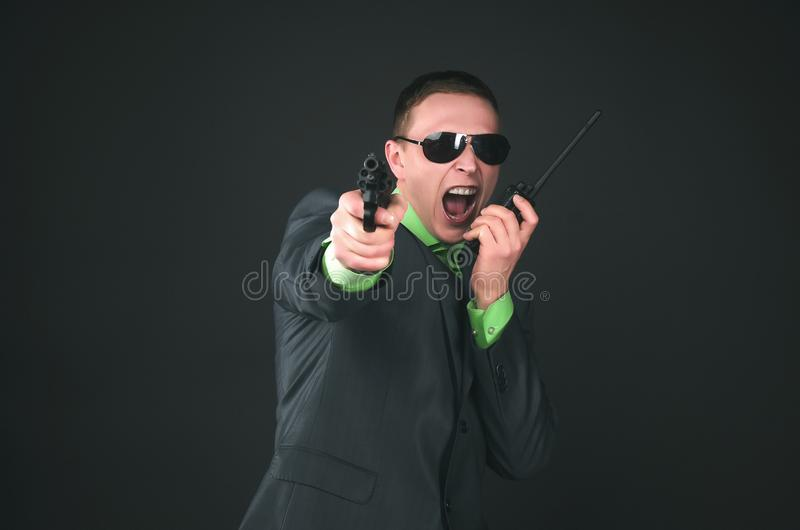 Spy. Bodyguard. Secret service agent. Security agent man in suit and sunglasses is shooting from a gun in his hand and is asking for assistance on the radio stock images