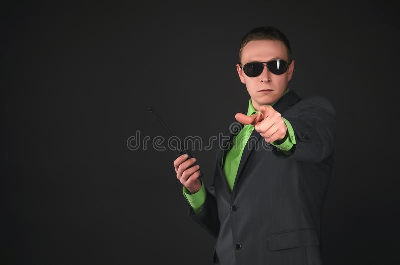 Spy. Bodyguard. Secret service agent. Security agent with the portable radio station is showing forward by his index finger isolated on black background with royalty free stock image