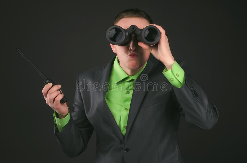 Spy. Spy or face control agent is looking through a binoculars in his hand and is holding on the portable radio station isolated on black background royalty free stock photo