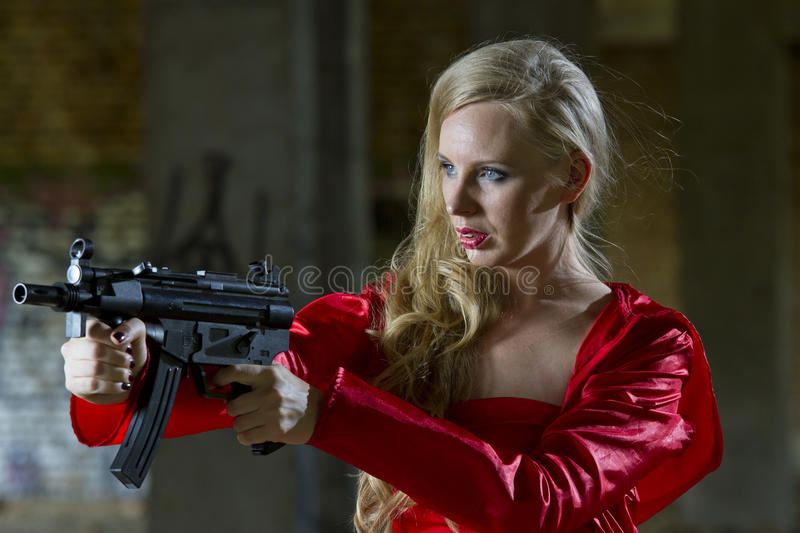 Spy with machine gun. Female spy in red dress and raincoat holding machine gun - outdoor stock images
