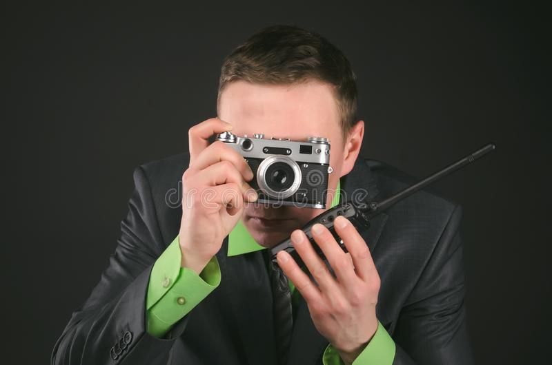 Security. Spy secret service agent with photo camera is photographing a compromising evidence and is talking on a portable radio station isolated on the black royalty free stock photo