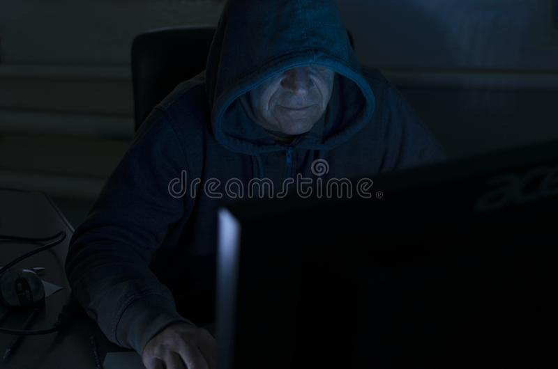 Spy sits at the computer at dark night. Blue light from screen on the hacker`s face. Hacker`s back who sitting against screen and hacking the system in the royalty free stock images