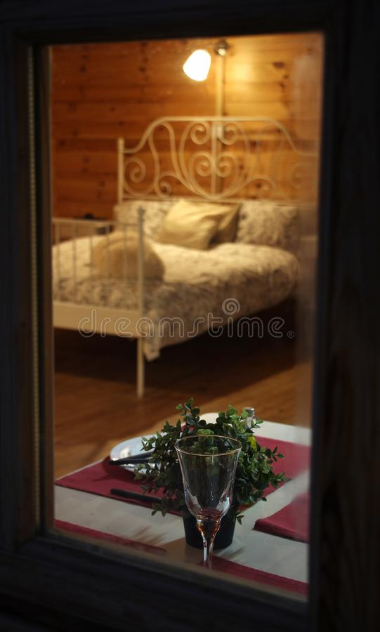Spy view through window of wooden country house, made bed, set table for romantic dinner, glass of wine, plates and nightlight,. Spy view through window of stock images
