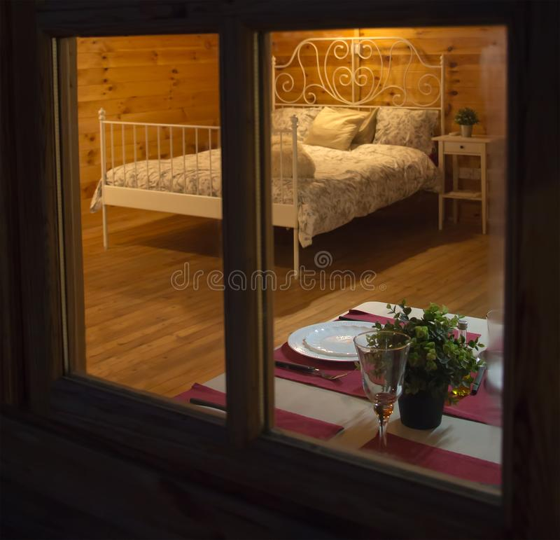 Spy view through window of wooden country house, made bed, set table for a romantic dinner, a glass of wine and plates, a secret. Spy view through the window of stock image