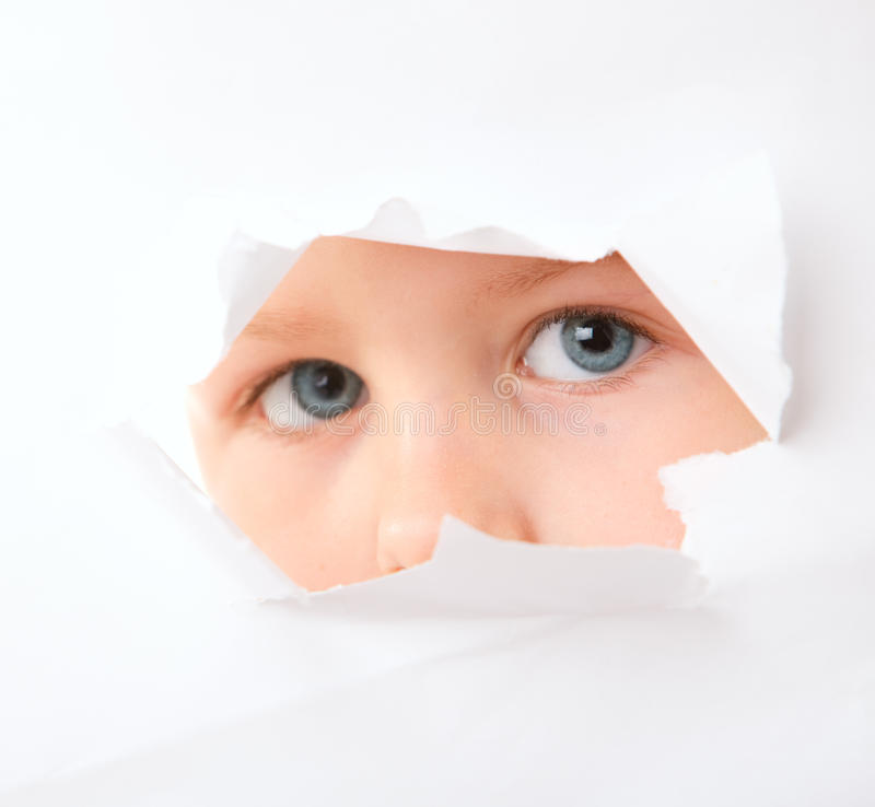 Spying. Cute little boy looking through paper hole stock photography